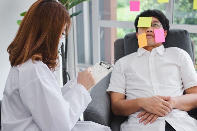 Giovane medico femminile asiatico con la lavagna per appunti che diagnostica l'uomo sovraccarico disabile di affari immagini stock