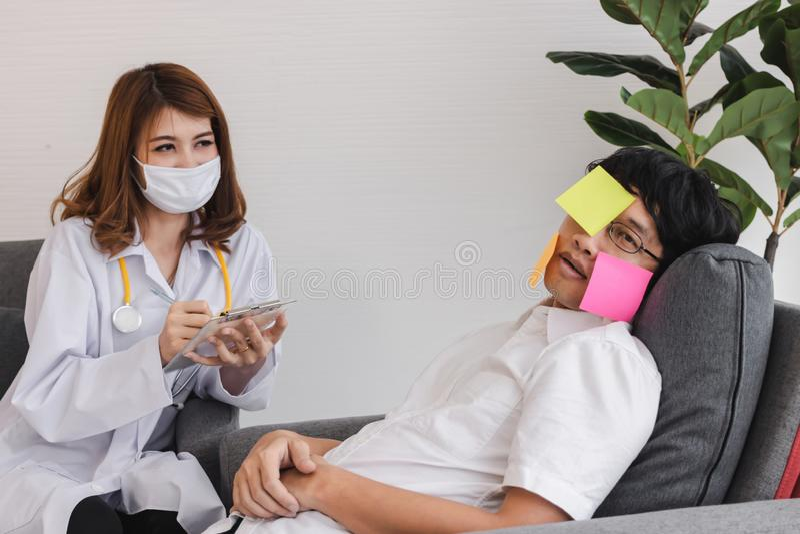 Giovane medico femminile asiatico con la lavagna per appunti che diagnostica l'uomo sovraccarico disabile di affari immagine stock libera da diritti