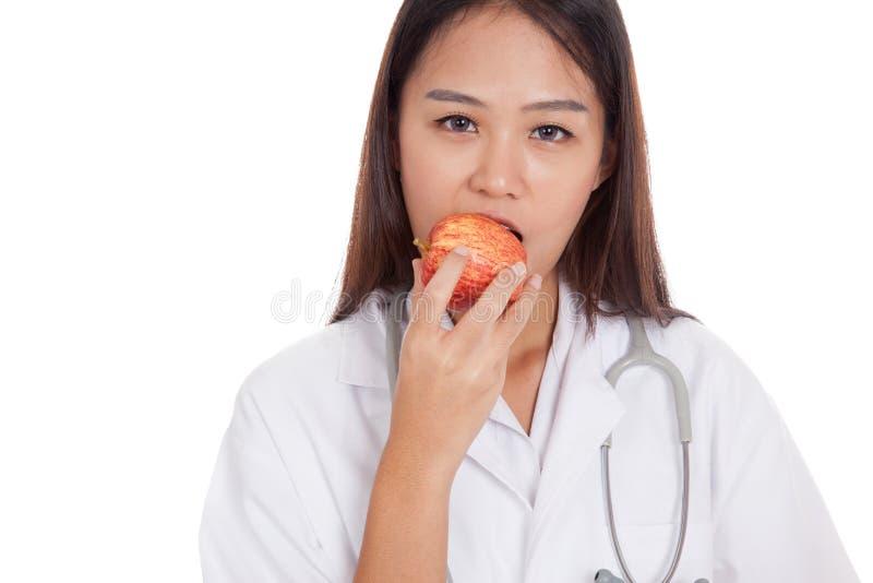 Giovane medico femminile asiatico mangia la mela immagini stock libere da diritti
