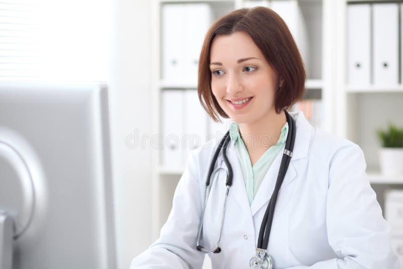 Giovane medico femminile castana che si siede ad uno scrittorio e che lavora al computer all'ufficio dell'ospedale fotografia stock libera da diritti