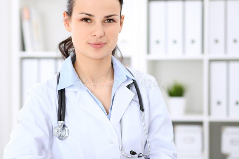 Giovane medico femminile castana che si siede alla tavola e che lavora all'ufficio dell'ospedale fotografia stock libera da diritti