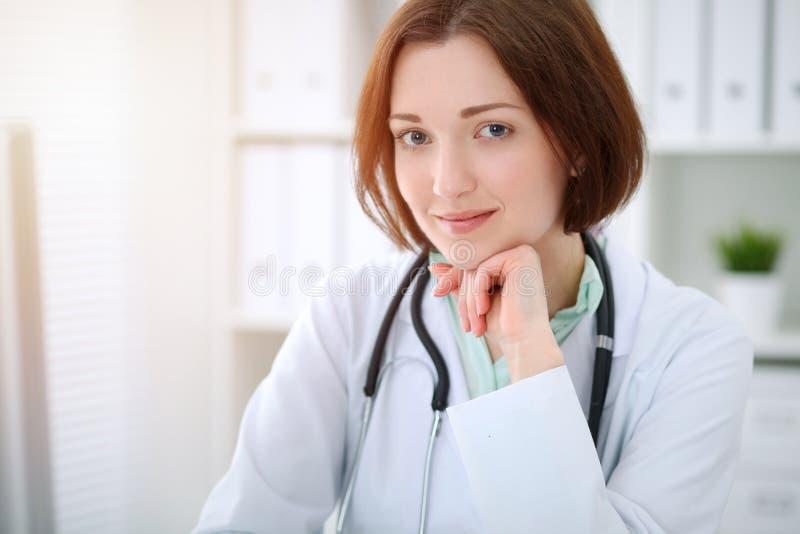 Giovane medico femminile castana che si siede alla tavola e che lavora con il computer all'ufficio dell'ospedale immagini stock