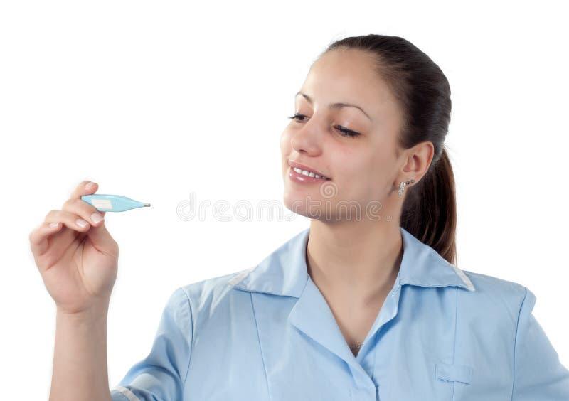Giovane medico femminile che esamina termometro fotografia stock libera da diritti