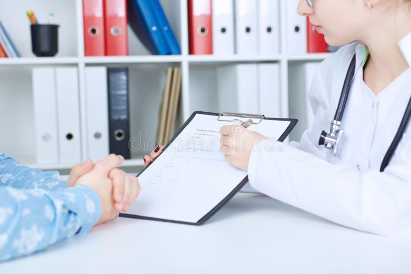 Giovane medico femminile che parla con suo paziente maschio all'ufficio Sanità e concetto medico immagini stock libere da diritti