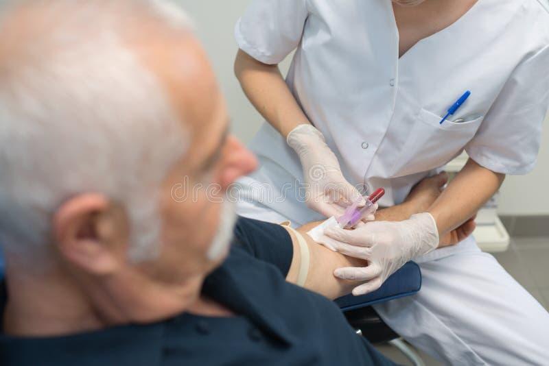 Giovane medico femminile che preleva a pazienti senior campione di sangue fotografia stock libera da diritti