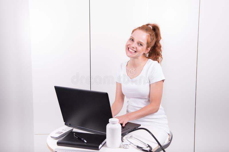 Giovane medico femminile dai capelli rossi nell'ufficio sta lavorando al patie fotografia stock libera da diritti