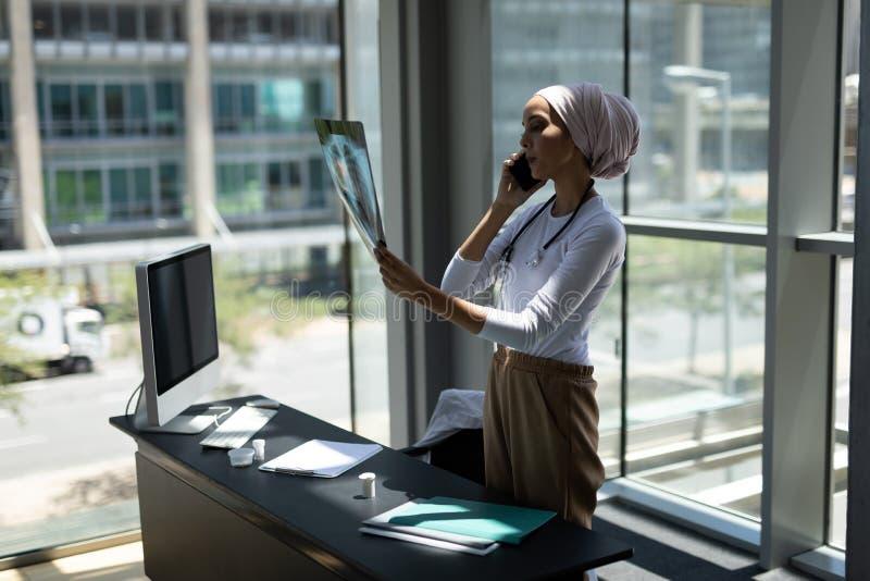 Giovane medico femminile razza mista che parla sul telefono cellulare mentre esaminando rapporto dei raggi x fotografia stock