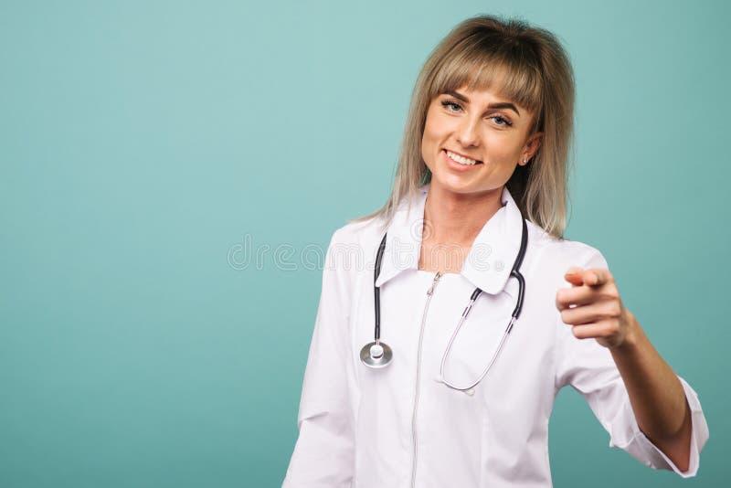 Giovane medico femminile sorridente con i punti di uno stetoscopio nella macchina fotografica con le sue dita fotografia stock