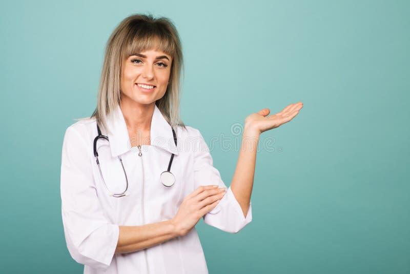 Giovane medico femminile sorridente con uno stetoscopio mostra qualcosa sulla palma immagini stock