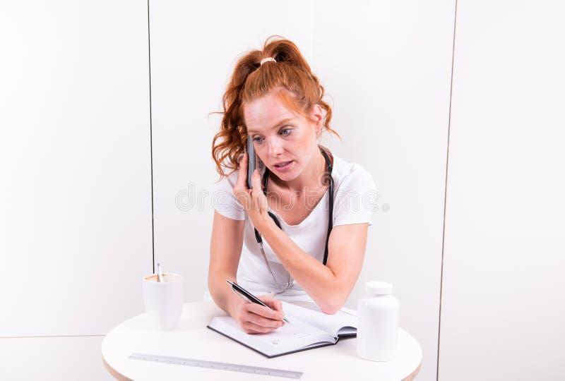 Giovane medico femminile sta prendendo le note durante la telefonata immagine stock