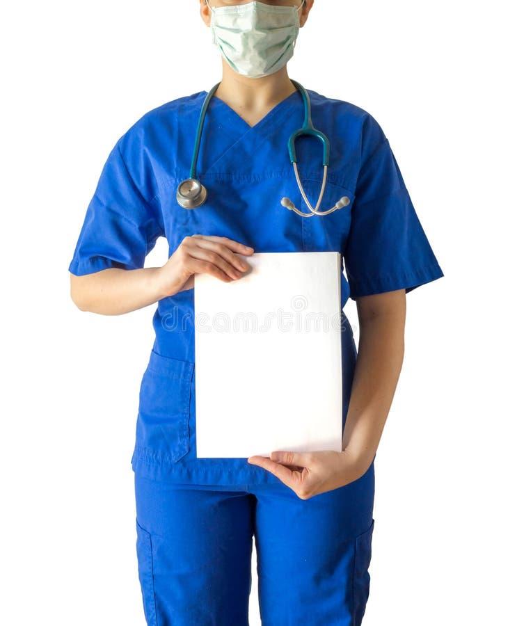 Giovane medico femminile in uniforme medica blu che indica un vuoto immagini stock