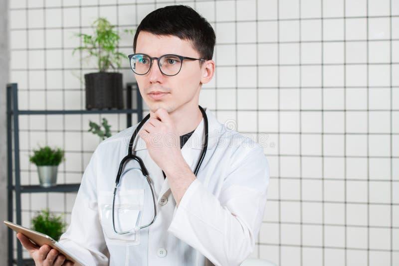 Giovane medico maschio bello pensieroso facendo uso del computer della compressa Tecnologie nel concetto della medicina immagine stock