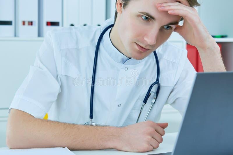 Giovane medico maschio caucasico che lavora allo scrittorio con il computer portatile sul fondo dell'ospedale immagini stock libere da diritti