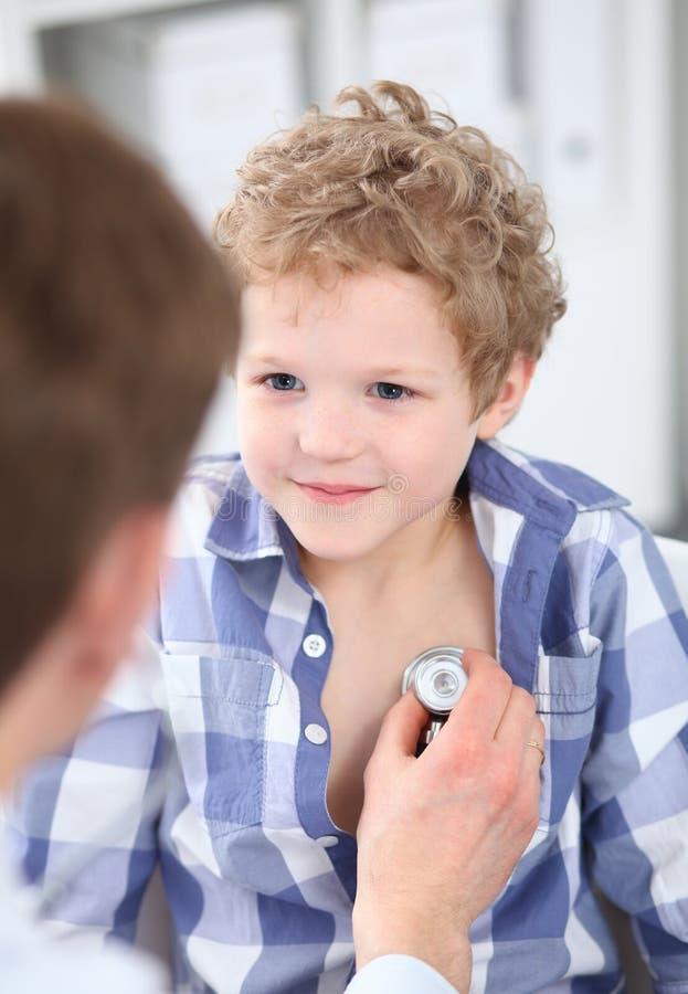 Giovane medico maschio che auscultating un piccolo ragazzo riccio dallo stetoscopio fotografia stock libera da diritti