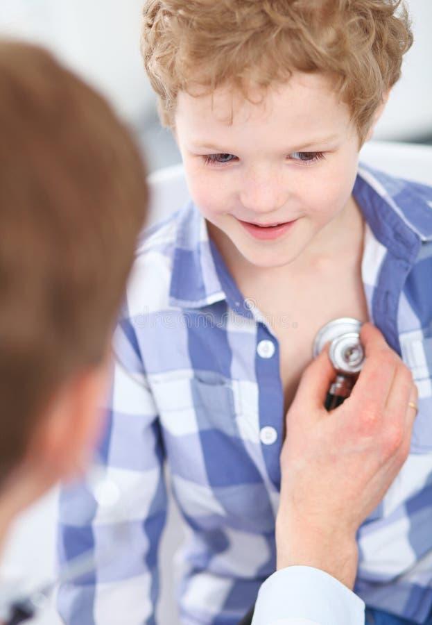 Giovane medico maschio che auscultating un ragazzino dallo stetoscopio Sanità, assicurazione e concetto di aiuto fotografia stock