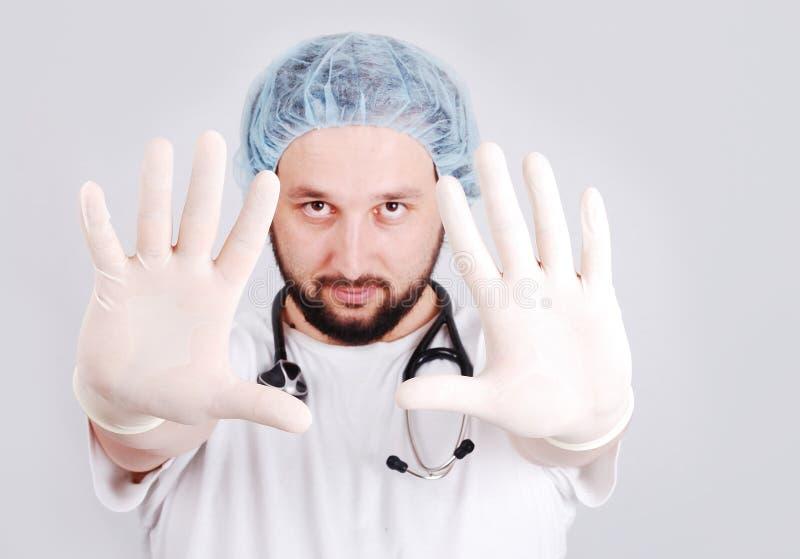 Giovane medico maschio con le mani nella parte anteriore e nella chirurgia immagini stock