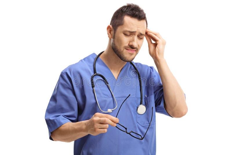 Giovane medico maschio con un'emicrania immagini stock libere da diritti