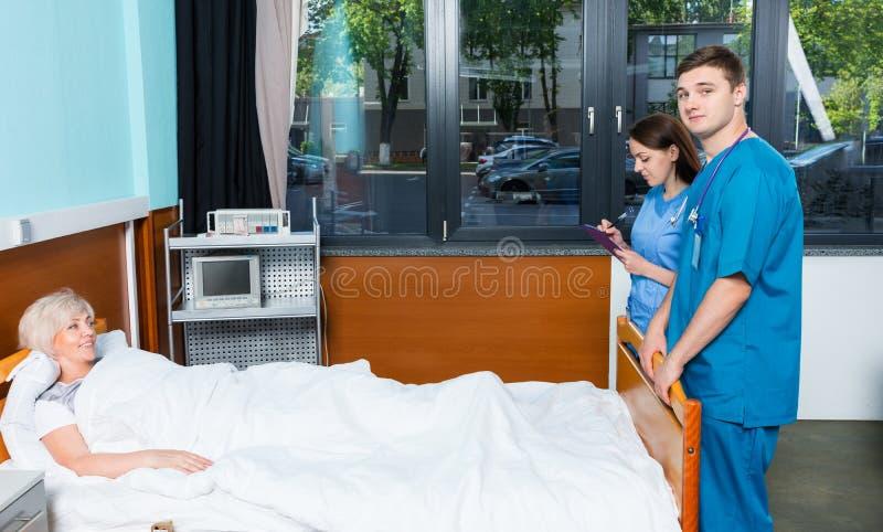 Giovane medico maschio ed infermiere femminile che visitano e che annotano COM immagine stock libera da diritti