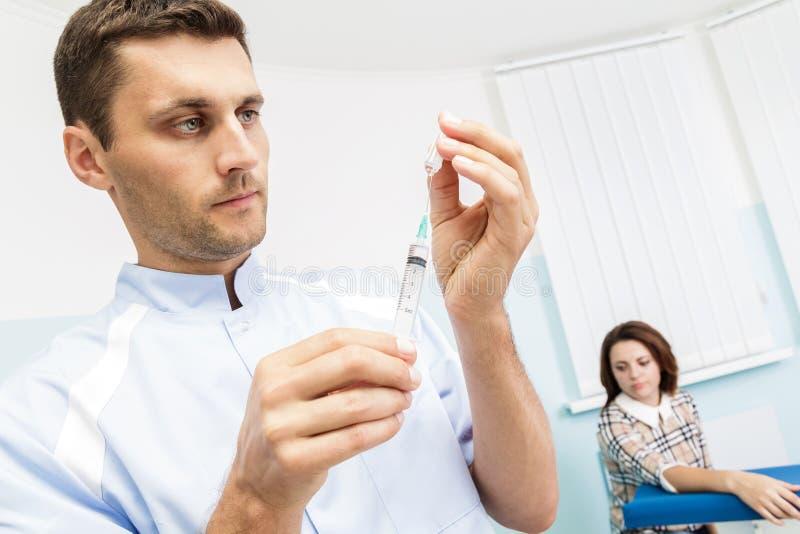 Giovane medico maschio prepara una medicina nella siringa nell'ufficio Medico che tiene una siringa fotografia stock libera da diritti