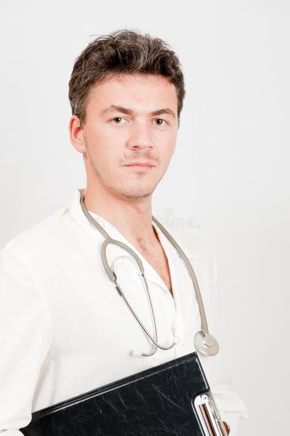 Giovane medico maschio serio con un dispositivo di piegatura immagine stock