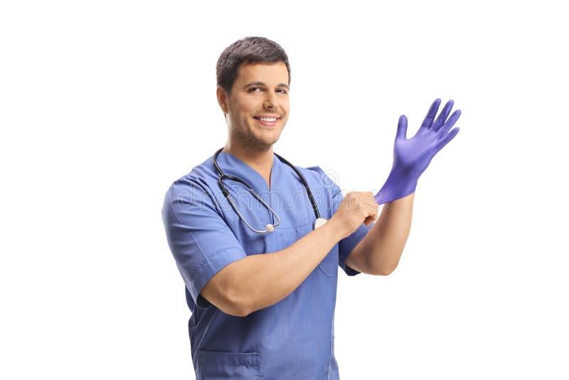 Giovane medico maschio sorridente che mette un guanto fotografia stock libera da diritti