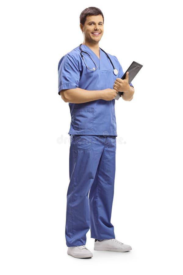 Giovane medico sorridente che posa e che tiene una lavagna per appunti fotografia stock