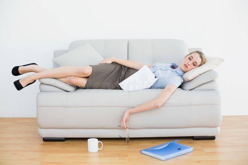 Giovane menzogne esaurita di sonno della donna di affari sul suo strato immagine stock
