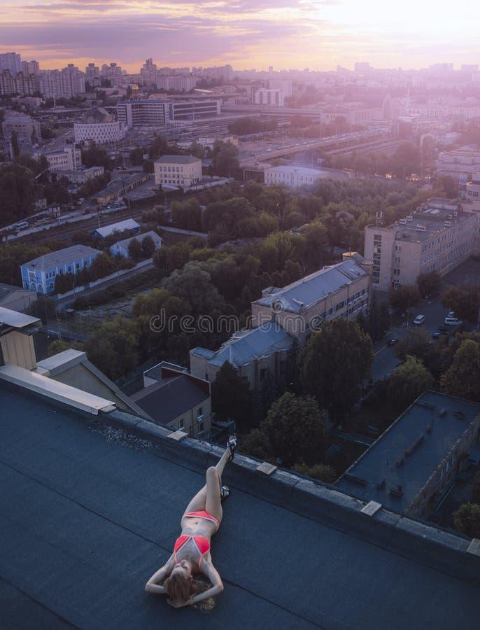 Giovane menzogne femminile e prendere il sole sul tetto e sui precedenti della vista della città Giorno, fuori immagini stock