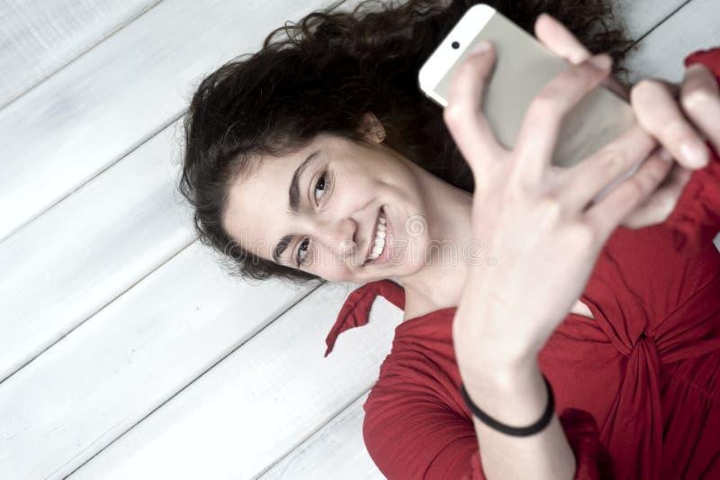 Giovane menzogne femminile sul pavimento che prende selfie fotografie stock libere da diritti