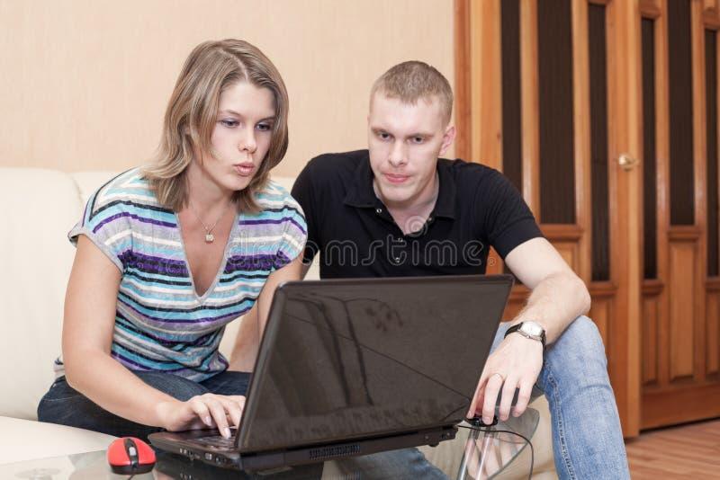 Giovane messaggio caucasico preoccupato della lettura della coppia sposata sullo schermo del computer portatile nella stanza dome fotografie stock