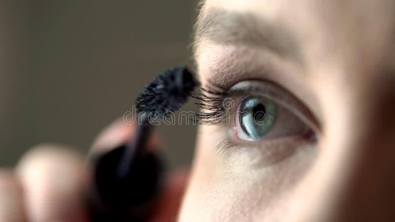Giovane mettere di modello sulla mascara e cigli volumizing, trucco e bellezza immagini stock libere da diritti