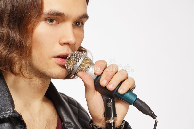 Giovane microfono bello della tenuta del cantante rock fotografia stock