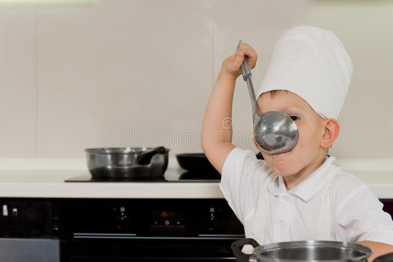 Giovane minestra dell'assaggio del cuoco unico dalla siviera immagine stock