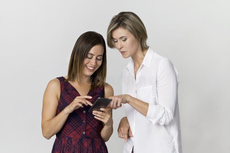 Giovane modello adulto di felicità due facendo uso dello smartphone su fondo bianco fotografie stock