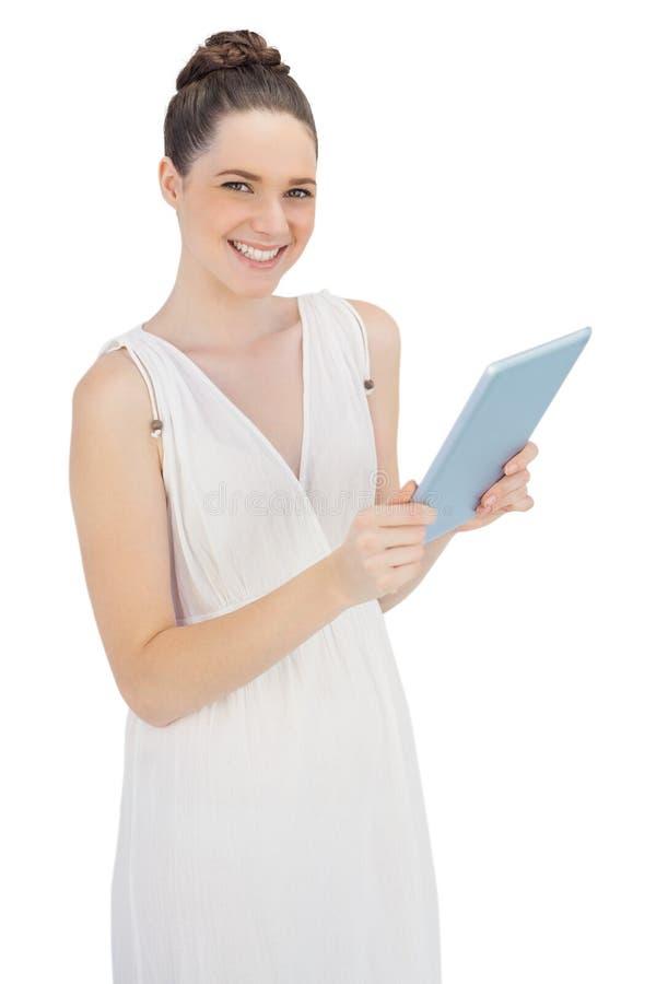 Giovane modello allegro in pc bianco della compressa della tenuta del vestito fotografia stock libera da diritti