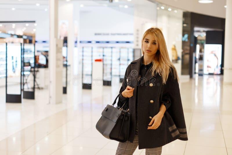 Giovane modello biondo moderno della donna in un cappotto alla moda elegante con una borsa nera di cuoio alla moda di modo immagine stock