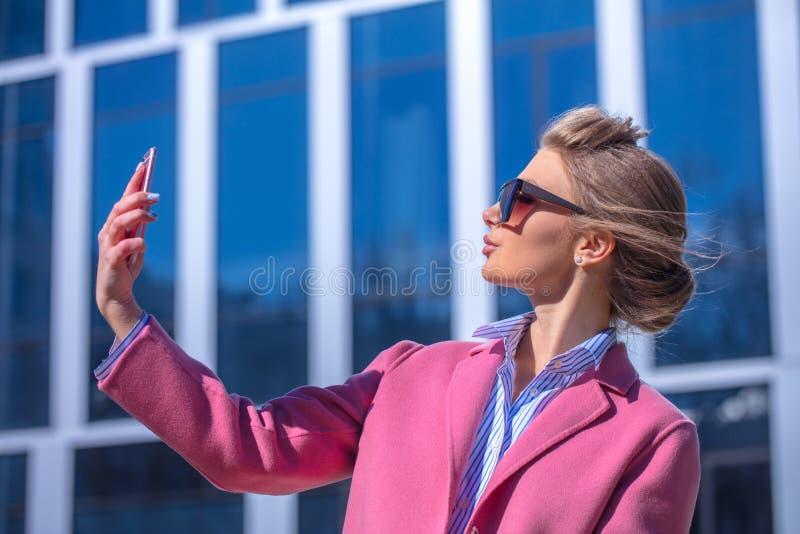 Giovane modello in cappotto rosa che prova a prendere foto immagine stock libera da diritti