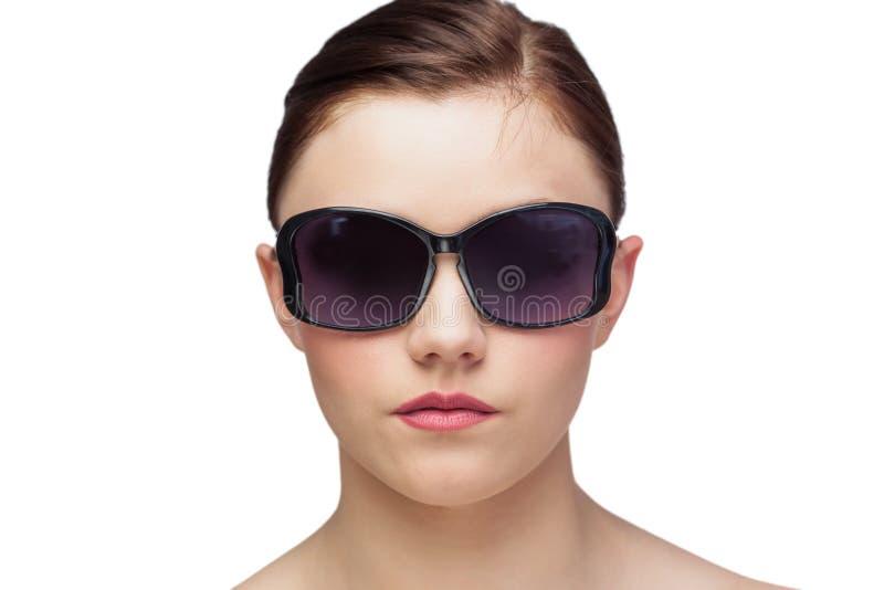 Giovane modello che indossa gli occhiali da sole di classe fotografia stock