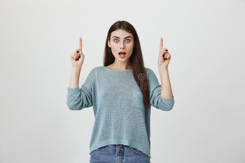 Giovane modello colpito e sorpreso che indica su con i dito indice e che esprime stupefazione con il linguaggio del corpo, ampi o fotografia stock
