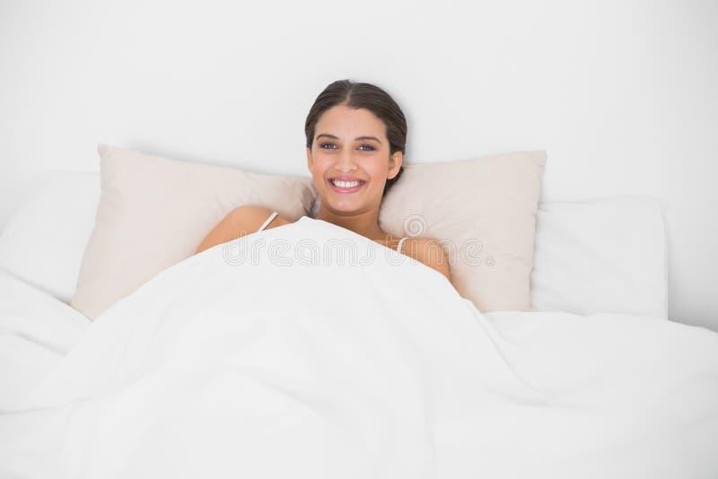 Giovane modello dai capelli marrone pacifico in pigiami bianchi che si trovano nel suo letto immagini stock libere da diritti