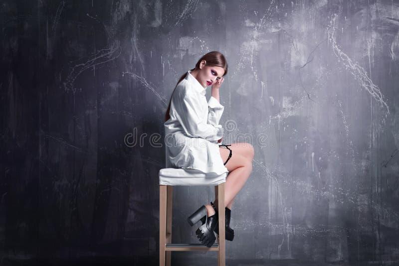 Giovane modello esagerato che si siede sulla sedia fotografie stock libere da diritti