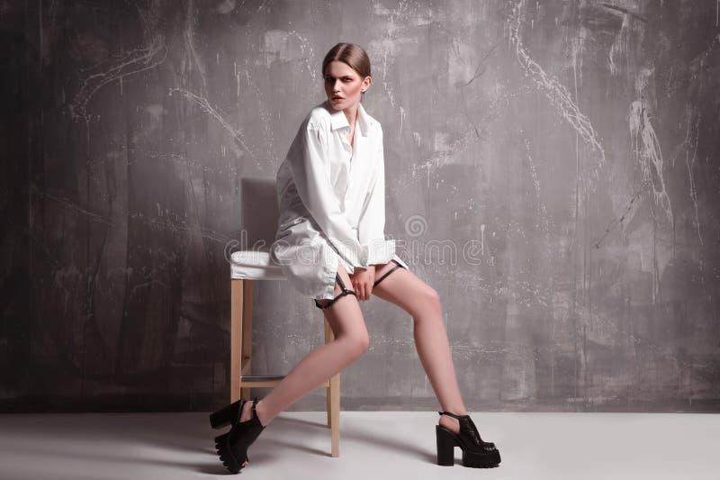 Giovane modello esagerato che si siede sulla sedia fotografia stock