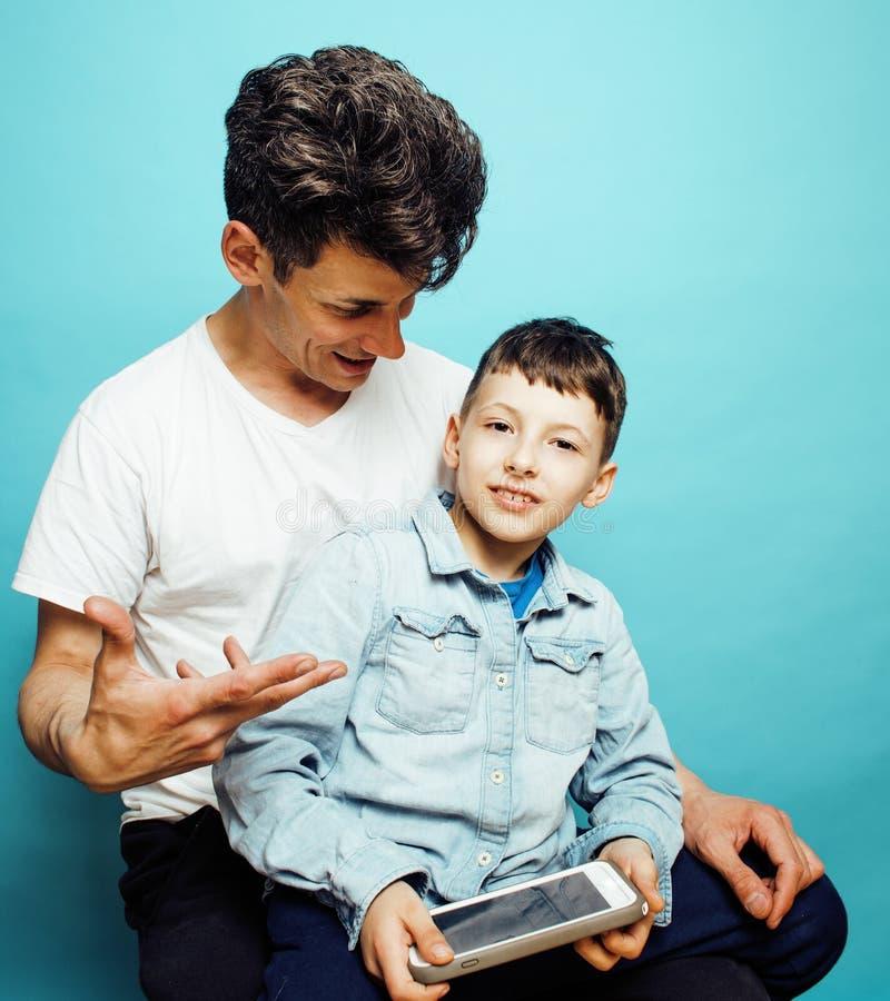 Giovane modello grazioso dell'uomo con il piccolo figlio sveglio che gioca insieme, concetto moderno della gente di stile di vita immagine stock libera da diritti