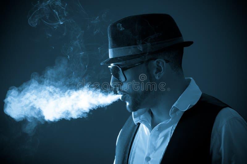 Giovane modello maschio alla moda bello che fuma a fotografia stock