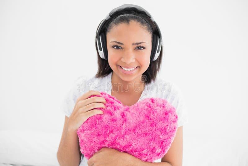 Giovane modello moro allegro che stringe a sé un cuscino e che ascolta la musica immagini stock libere da diritti