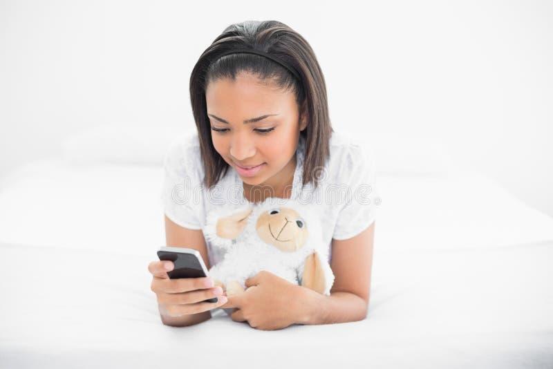 Giovane modello moro concentrato che stringe a sé una pecora della peluche e che esamina il suo telefono cellulare fotografia stock