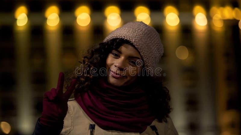 Giovane modello ottimista che posa alla macchina fotografica e che mostra il segno della mano di vittoria, pace fotografie stock libere da diritti