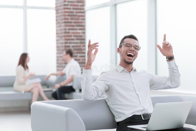 Giovane moderno con il computer portatile che si siede sul sof? dell'ufficio fotografie stock