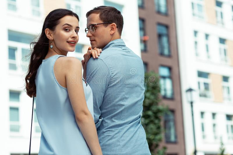 Giovane moglie che tocca spalla del suo marito bello immagini stock