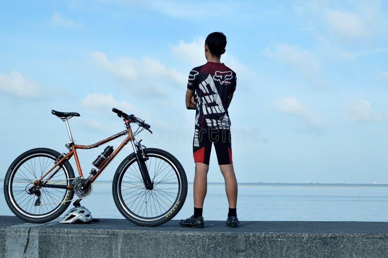 Giovane motociclista maschio che sta accanto alla sua bicicletta della montagna sull'acqua della rottura dell'oceano fotografie stock libere da diritti